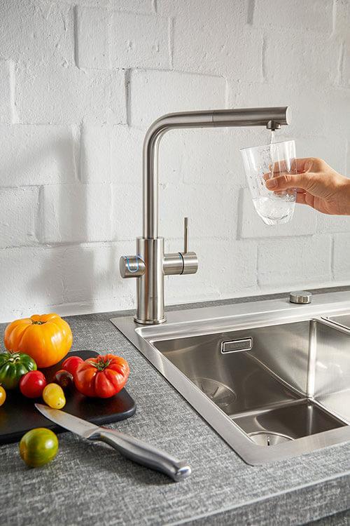 Wasserhahn in Silber mit Wasserglas