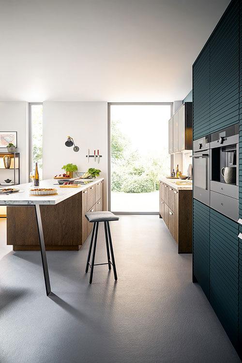 Seitenansicht - Rocco Küche von Systhema Holzoptik mit Sitzgelegenheit und separaten Schrank für E-Geräte in Petrol