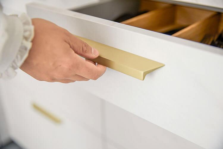 Hand öffnet Schublade vom formschönen Griff in Goldoptik