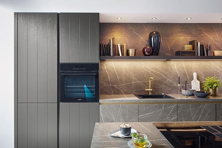 Küche Taran von Systhema in dunkler Marmornachbildung mit Spülbecken - hocheingebauter Herd im grauen Schrank in Holzoptik