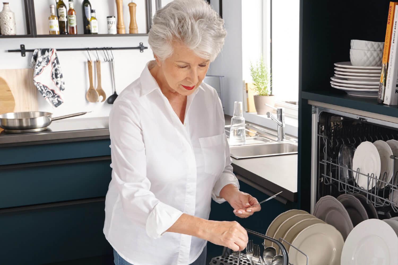 Frau räumt hocheingebauten Siena Geschirrspüler aus