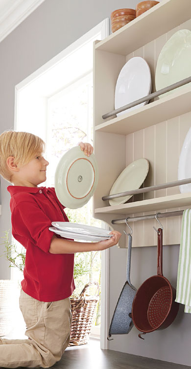 Systhema Küche Caneto in sandgrau-satin - Junge räumt Teller ins offene Regal auf