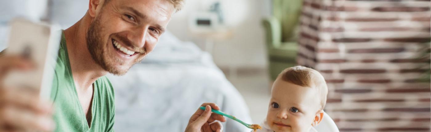 Mann füttert Baby und macht Selfie