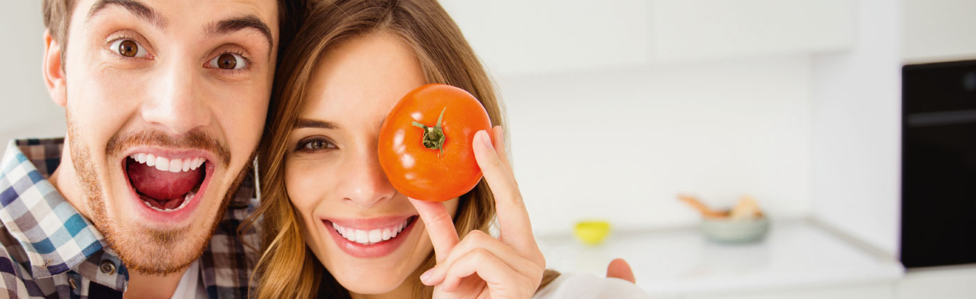 Gesichter von einem Mann und einer Frau - Frau hält Tomate vor einem Auge